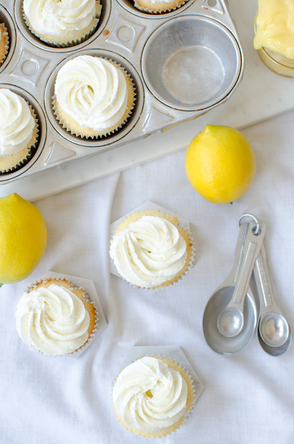 An easy but impressive cupcake - vanilla cupcakes stiffued with lemon curd and topped with lemon buttercream frosting!